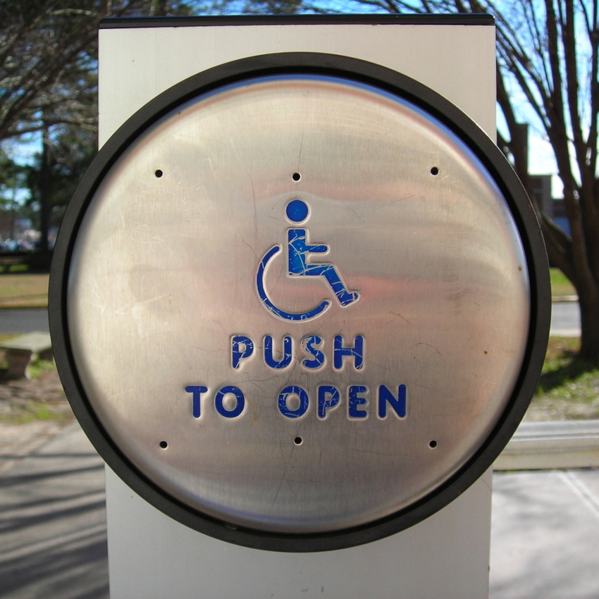 Photo of a door opener button with the words
